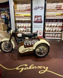 """Eine ganze Nische gestaltete Mars für seine Schokoladenmarke """"Galaxy"""" (a.k.a. DOVE) im Flughafen von Lissabon mit einem retroesken Motorrad mit Beisitzer anlässlich der Einführung der neuen Dove-Stäbchen-Portionen."""