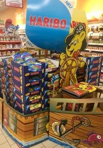 Haribo investiert in den neuen Piratenmix und umkränzt zwei Paletten mit einem Pappschiffsrumfp und Pappbug. Noch ein auffälliges blaues Segel aus Pappe und ein Goldbär am Steuerrad darauf - fertig ist der effektivolle Aufsteller.