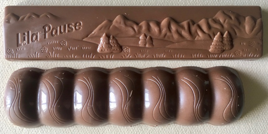 Die Formen der nackten Riegel unterscheidet sich deutlich: 7 Kammern bietet der neue Riegel, der übrigens auffällig kürzer ist und 1,5 Gramm leichter, aber die alte Lila Pause hatte dieses wunderschöne Relief einer Alpenlandschaft eingeprägt. Das war wirklich etwas besonderes, sehr hochwertig für einen Pfennigartikel und ist, wenn es nach Mondelez geht, unwiederbringbar verloren.